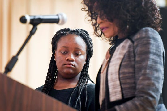 "Mishonte Mills listens as Rev. Robbie Williams reads a piece she wrote during a bullying and youth violence forum at the Grant Center in Asheville May 28, 2019. ""My topic is the abuse and violence that I face on a daily basis,"" Mills wrote, ""In my neighborhood, I hear gunshots every night."""