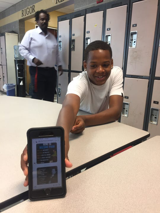 Brian Lawrence shows a motivational text from Rashaan Hornsby, whose Education Over Everything teaches young people in the city about personal finance, entrepreneurship and small business ownership.
