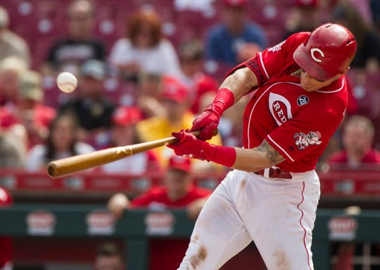 Cincinnati Reds first baseman Derek Dietrich (22) hits a base hit in the bottom of the sixth inning of the MLB National League game between Cincinnati Reds and Pittsburgh Pirates at Great American Ball Park in Cincinnati on Whednesday, May 29, 2019.