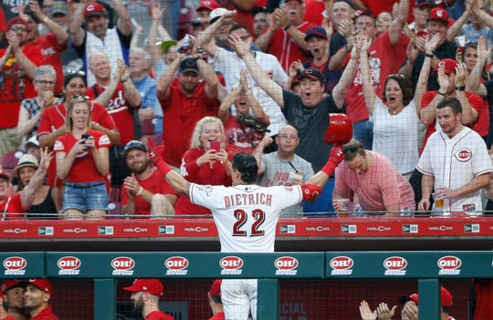 Cincinnati Reds' Derek Dietrich (22) acknowledges the fans following a two-run home run off Pittsburgh Pirates relief pitcher Geoff Hartlieb, his third of the game, during the seventh inning of a baseball game, Tuesday, May 28, 2019, in Cincinnati.