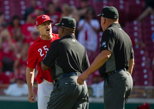 Cincinnati Reds manager David Bell (25) yells at umpire Jeff Nelson (45) as umpire Laz Diaz (63) holds him back after Cincinnati Reds third baseman Eugenio Suarez (7) was hit by a Pittsburgh Pirates relief pitcher Clay Holmes (52) in the eighth inning of the MLB National League game between Cincinnati Reds and Pittsburgh Pirates at Great American Ball Park in Cincinnati on Whednesday, May 29, 2019. Pittsburgh Pirates defeated Cincinnati Reds 7-2. umpire Jeff Nelson (45) threw him out of the game.