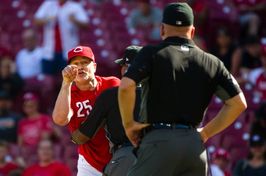 Cincinnati Reds manager David Bell (25) yells at umpire Jeff Nelson (45) as umpire Laz Diaz (63) holds him back after Cincinnati Reds third baseman Eugenio Suarez (7) was hit by a Pittsburgh Pirates relief pitcher Clay Holmes (52) in the eighth inning of the MLB National League game between Cincinnati Reds and Pittsburgh Pirates at Great American Ball Park in Cincinnati on Whednesday, May 29, 2019. Cincinnati Reds manager David Bell (25) was thrown out of the game. Pittsburgh Pirates defeated Cincinnati Reds 7-2.