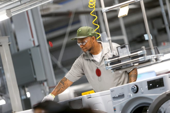 Workers put together washing machines in their final stages at the grand opening of the LG Clarksville plant in Clarksville, Tenn., on Wednesday, May 29, 2019.