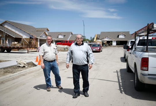 Fort Dodge builders Mike McCarville, left, and Jim Kesterson walk around a housing construction site on Thursday, May 23, 2019. The builders have been instrumental in building new housing facilities to help serve the needs of a population increase brought on by the new Prestage Foods plant in nearby Eagle Grove.