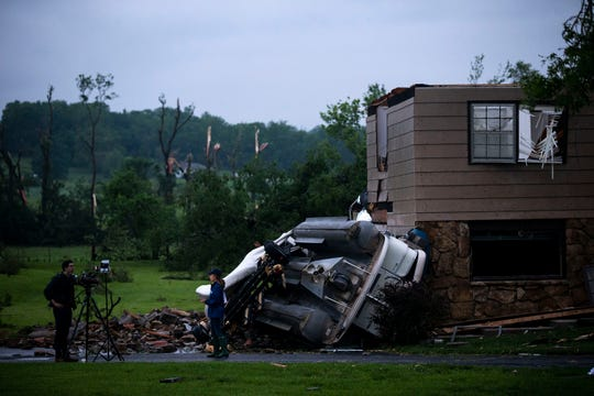 Television journalists report from outside of a home significantly damaged by a tornado on Wednesday, May 29, 2019 in rural Lawrence, Kansas.
