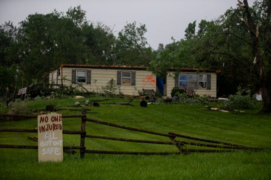 A homemade sign declares no injuries outside a damaged home on Wednesday morning, May 29, 2019 in rural Lawrence, Kansas, following a tornado the evening before.