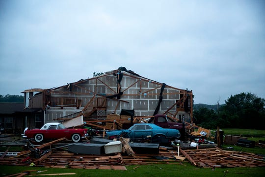 Cars sit where a garage once stood on Wednesday, May 29, 2019 in rural Lawrence, Kansas, after a tornado caused significant damage the following evening.