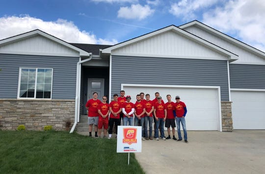 This year's Carlisle Community School District's Building Trades students pose outside their completed 1600 sq. ft 3-bedroom house.