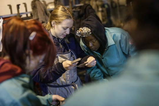 Jazmond Ravarra of Detroit looks closely as Women Who Weld founder and instructor Samantha Farr (center) helps her measure to make drill holes on a metal plate to be used in building a lamp at the Addison Iron Fabricators in Detroit on March 31, 2016.