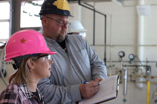 Richard Putnam discusses valve adjustments in Delta College's chemical processing lab with student-apprentice Teresa McCoy. The apprenticeship program has proven a win-win for Dow and Delta students who earn while they learn.