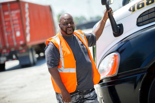 In this Wednesday, May 22, 2019 photo, Leon Brown stands by his tractor-trailer after making a delivery from a distribution center to the Port of Savannah, in Garden City, Ga. Brown is trusted enough to drive a tractor-trailer inside one of the nation's busiest seaports more than six years after being released from prison. But he's not allowed to vote in Georgia because of a law rooted in the years after the Civil War when whites sought to keep blacks from the ballot box.