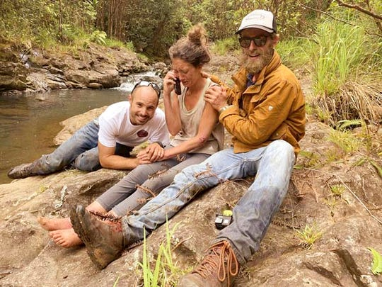 In this Friday, May 24, 2019, photo provided by Troy Jeffrey Helmer, shows Amanda Eller, second from left, after being found by searchers, Javier Cantellops, far left, and Chris Berquist, right, above the Kailua reservoir in East Maui, Hawaii, on Friday afternoon. The men spotted Eller from a helicopter and went down to retrieve her.