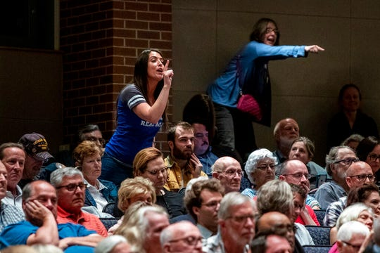 President Donald J. Trump supporters, including Grand Rapids resident Anna Timmer, left, heckle U.S. Rep. Justin Amash, R-Cascade Township, at Grand Rapids Christian High School's DeVos Center for Arts and Worship on Tuesday, May 28, 2019.