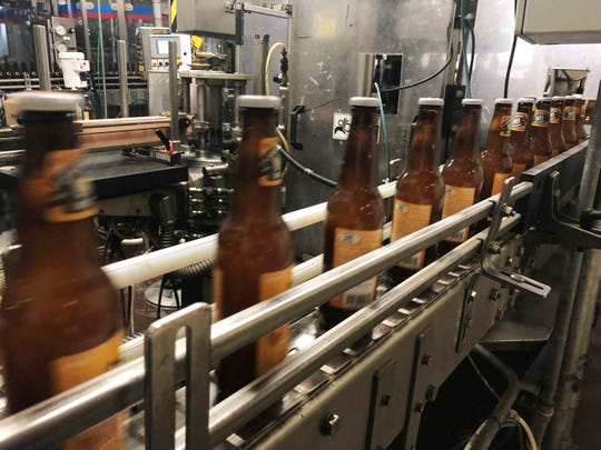 Bottles, freshly filled with beer, move on a belt at Lakefront Brewery in Milwaukee.