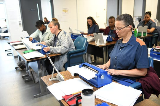 Julia Lyons-Davis, right, and other inmates work on their manuscripts, transcribing novels into braille to become certified by the Library of Congress, at the Women's Huron Valley Correctional Facility in Ypsilanti, Mich. on May 28, 2019.  Twenty inmates have been learning to transcribe braille and seven have passed their first certification.