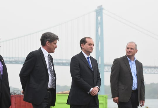 Daniel Deane (from left), president, of the Nicholson Terminal and Dock Company, stands with U.S. Secretary of Labor Alexander Acosta, and Patrick Sutka, treasurer of Nicholson Terminal and Dock Company, during a tour the Port of Detroit Nicholson Terminal on Wednesday, May 29, 2019. The Ambassador Bridge stands in the distance.