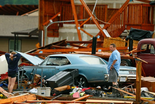 A man and woman inspect the damage to their home and classic cars after being hit by a tornado on Tuesday, May 28, 2019, in a neighborhood south of Lawrence, Kansas. The past couple of weeks have seen unusually high tornado activity in the U.S., with no immediate end to the pattern in sight.