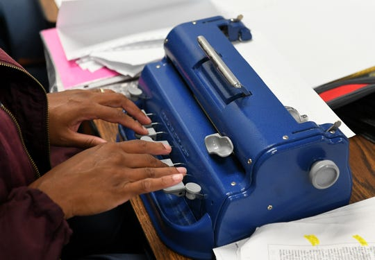 Tashiena Combs, 43, and other inmates work on their manuscripts, transcribing novels into braille to become certified by the Library of Congress, at the Women's Huron Valley Correctional Facility in Ypsilanti, Mich. on May 28, 2019. Here, she presses keys on the braillewriter. Twenty inmates have been learning to transcribe braille and seven have passed their first certification.