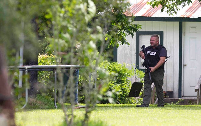 Law enforcement investigates a home where they believe the suspect's vehicle from an officer-involved shooting is parked, Wednesday, May 29, 2019, in Cleveland, Texas.