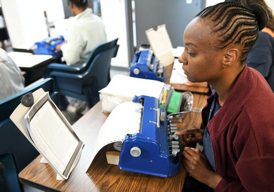 April Foster, 38, right, and other inmates work on their manuscripts, transcribing novels into braille to become certified by the Library of Congress, at the Women's Huron Valley Correctional Facility in Ypsilanti, Mich. on May 28, 2019.  Twenty inmates have been learning to transcribe braille and seven have passed their first certification.