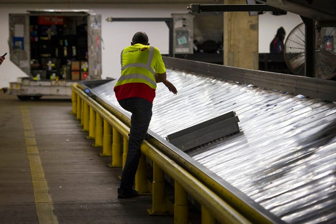 In this March 26, 2019, file photo, a baggage handler waits for luggage to arrive at Dulles International Airport in Dulles, Va. The Transportation Security Administration has changed its cannabis policy to allow passengers to travel with some forms of CBD oil and a drug derived from marijuana that has been approved by the Food and Drug Administration.