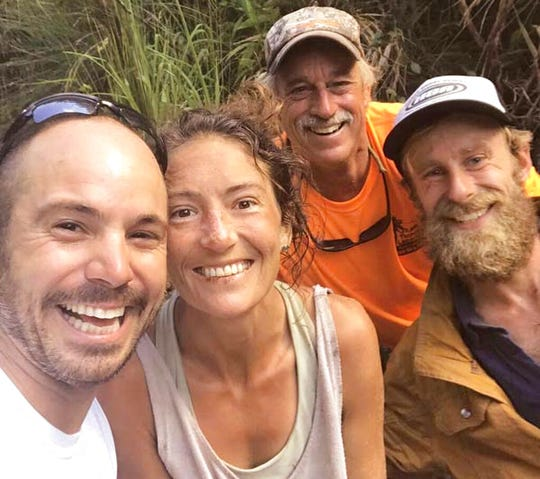 In this Friday, May 24, 2019, photo provided by Troy Jeffrey Helmer, resident Amanda Eller, second from left, poses for a photo after being found by searchers, Javier Cantellops, far left, Helmer and Chris Berquist above the Kailua reservoir in East Maui, Hawaii, on Friday afternoon.