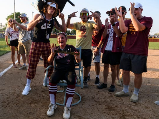 Gibson Southern's Lyndsi Adamson (3), bottom center, laughs as she complies with requests from friends, behind her, to sit in a chair following her team's IHSAA Class 4A softball regional win at Gibson Southern High School in Fort Branch, Ind., Tuesday, May 28, 2019.