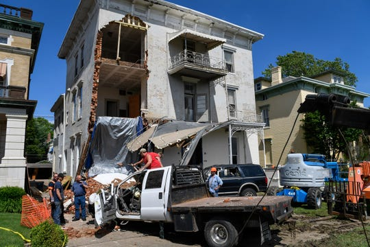 Workers with Feller Towing & Recovery and MCF Construction remove debris as they work to remove one of the two vehicles that have hit a historic home at 414 S.E. Riverside in the last few days, Wednesday, May 29, 2019.