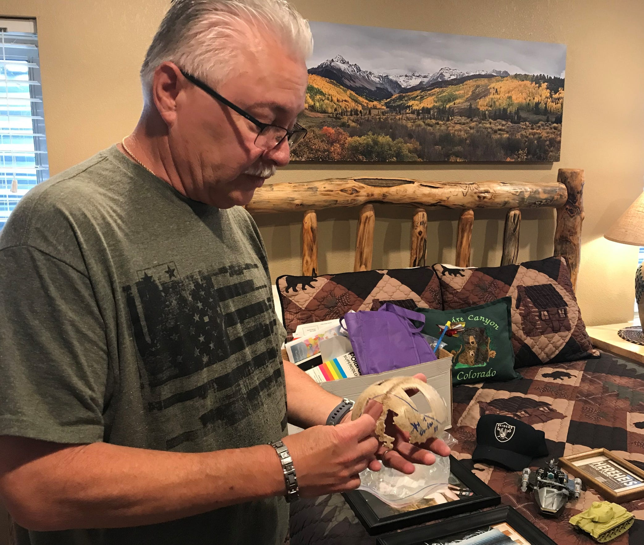 Allyn Atadero looks over the skull cap of his son Jaryd Atadero, who disappeared in the Roosevelt National Forest and was found dead nearly 20 years ago, while other reminders of Jaryd lie on a bed in his home in Parker.