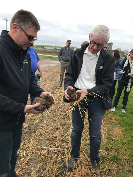 Nick Guilette of AgSource Laboratories, left, shows Gov. Tony Evers chunks of soil that were planted with a cover crop of rye to help prevent water runoff and erosion at Deer Run Dairy in Kewaunee.