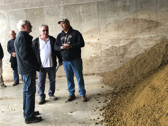 Gov. Tony Evers, foreground, talks with Deer Run Dairy operators Duane Ducat, middle, and Dale Bogart on Tuesday, May 28, about the farm's manure digester. The remains of the cleaned-up waste after processing are on the right.