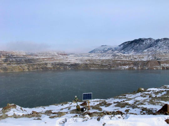 FILE - This Dec. 14, 2016 file photo shows Berkeley Pit in Butte. Atlantic Richfield wants to build a second treatment plant to lower the level of acidic, metal-laden water that has collected in a former mining pit in Butte that was closed more than 35 years ago, The Montana Standard reported Wednesday, May 29, 2019.   (AP Photo/Matt Volz, File)