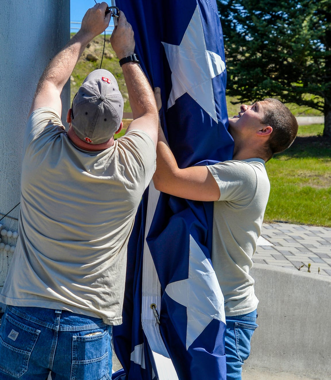Master Sergeant Mark Snodgrass, left, and Tech Sergeant Kevyn Waite switch out the flag at Broadwater Overlook Park Tuesday, May 28, 2019. The flags are changed out on a regular basis for cleaning and repairs.
