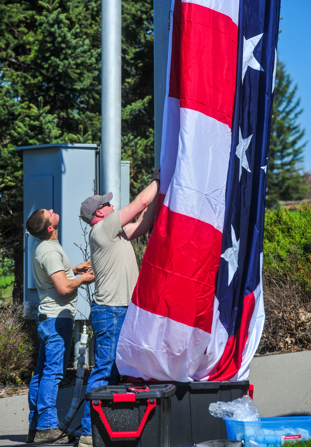 Master Sergeant Mark Snodgrass, right, and Tech Sergeant Kevyn Waite replace the flag at Broadwater Overlook Park Tuesday, May 28, 2019. The flags are changed out on a regular basis for cleaning and repairs.