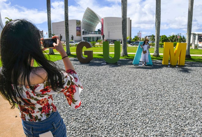 Tourists capture an image with a Guam sign at the Plaza de España in Hagåtña in this May 29 file photo.