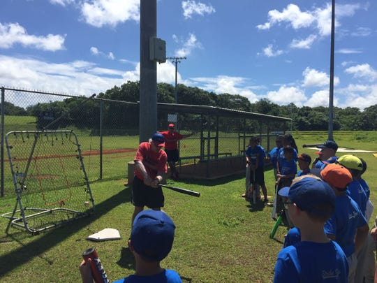 Coaches demonstrate basic batting skills for baseball camp goers at the 2018 camp.