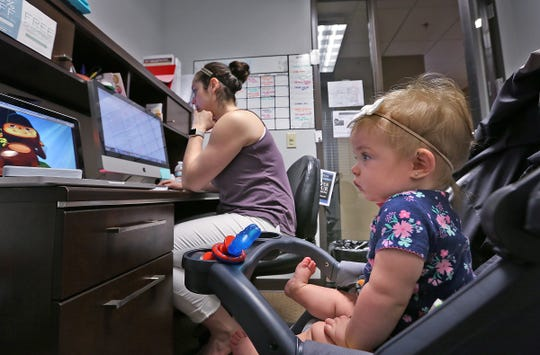 Bellamy Walker (foreground) watches cartoons while her mother, Lauren Edwards, works at the Keller Williams Realty Indy Metro Northwest offices. Keller Williams has been a Top Workplace in Central Indiana for 2018 and 2019.