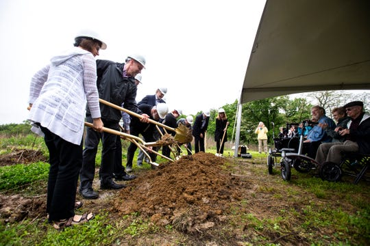 Officials, employees, builders turn dirt from their gold colored shovels during a groundbreaking ceremony, Wednesday, May 29, 2019, at the future site of Oaknoll East, along Scott Blvd, in Iowa City, Iowa.