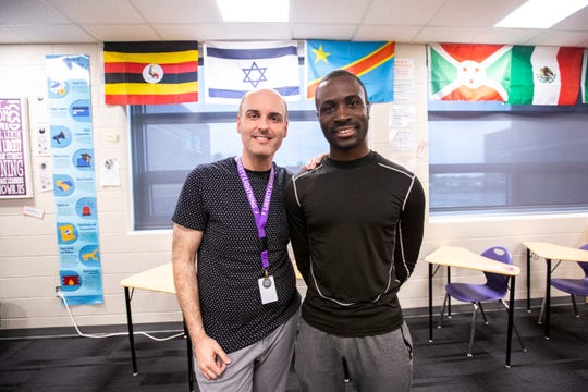 Héritier Otiom poses for a photo with teacher Daniel Lekin, left, Tuesday, May 21, 2019, at Liberty High School in North Liberty, Iowa.
