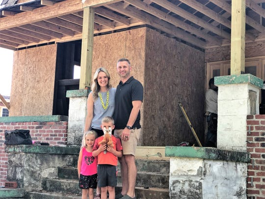 Lori and David Hensley, pictured with 5-year-old Owen and 4-year-old Stella Ruth outside the Gibbs Drive home they are rehabilitating on May 22, 2019.