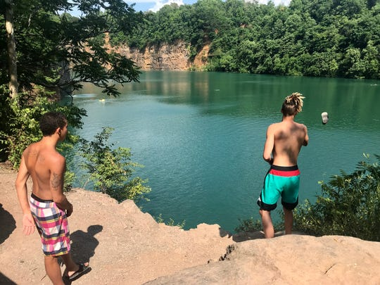 James Webb, right, tosses a flip-flop into Fort Dickerson's Augusta Quarry in South Knoxville as he prepares to jump. Austin Richard, left, prepares to jump next. Several people have died cliff jumping in recent years.