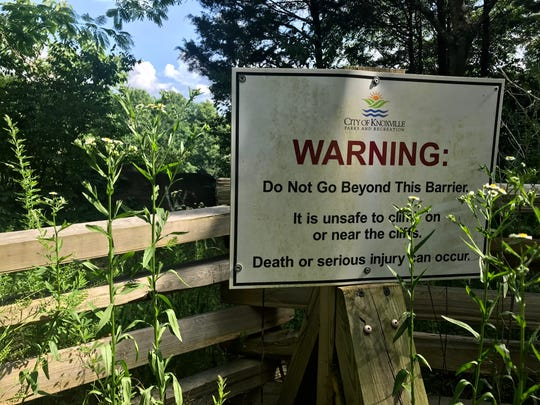 A sign sits on the top of a cliff at Fort Dickerson's Augusta Quarry in South Knoxville. Several people have died cliff jumping in recent years.