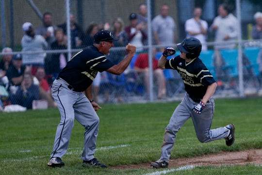 Delphi's Evan Fritz celebrates with coach Ryan Long after hitting a home run in the 2019 sectional championship against Central Catholic.