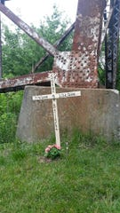 A cross and flowers stand near the Pope Lick trestle off Taylorsville Road in Louisville in memory of 15-year-old Savanna Bright, who was on the train tracks when she was fatally struck by a Norfolk Southern train May 26, 2019.