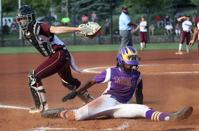 Male's Jasmine Miller slides in to home safe past the attempted tag by Assumption's Sydney Young on May 28, 2019