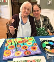 Grace McGuire, Gardens resident, along with Barb from Create and Converse, enjoy the wine and canvas painting class during senior week at Felician Village.