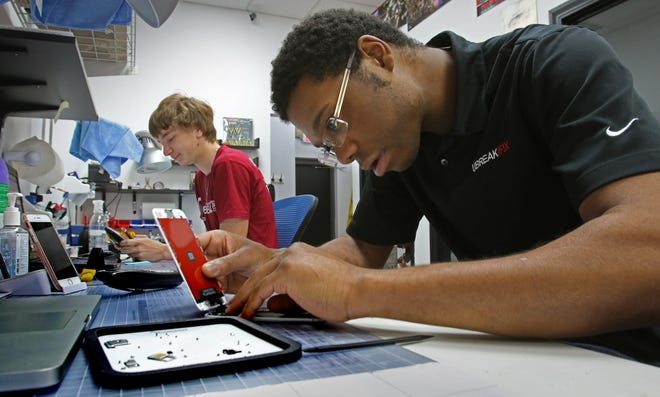 Alex Wright, manager of the Greenfield UbreakiFix, re-assembles an iPhone 6 that was water damaged for testing as Technician Michael Van Dehy works in the background. Another location for UbreakiFix opened recently in Greenfield.