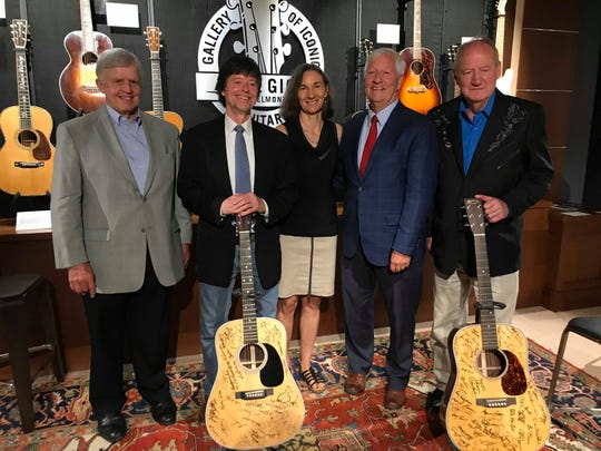(From left to right) Marty Dickens, Ken Burns, Julie Dunfey, Bob Fisher and Dayton Duncan stand with the signed guitars in Belmont's Gallery of Iconic Guitars.