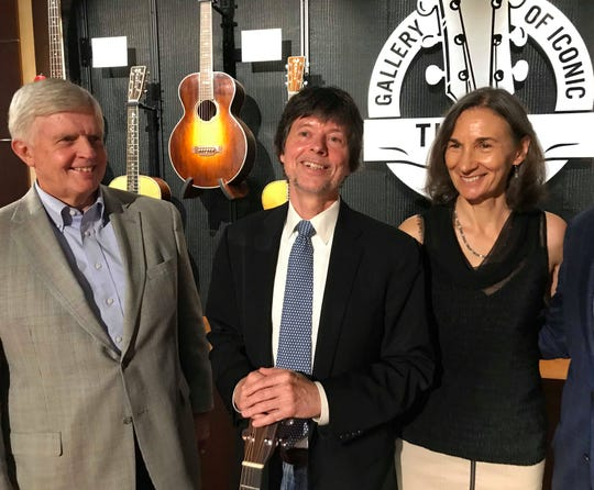Marty Dickens (left), Ken Burns (middle) and Julie Dunfey (right) pose for a photo at Belmont's Gallery of Iconic Guitars.