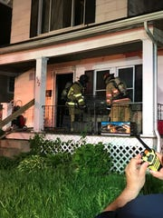 Newark firefighters remove aquariums from the home at 422 North Cedar Street Tuesday night, after fire which started on the back porch gutted the inside.
